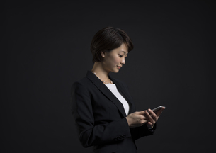 スマートフォンを操作するビジネス女性の写真素材 [FYI02973240]