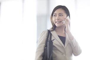スマートフォンで通話するビジネス女性の写真素材 [FYI02973256]