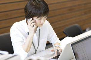 PCを見て電話をするビジネス女性の写真素材 [FYI02973257]