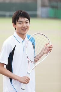 テニスラケットを持って笑う男子学生の写真素材 [FYI02973258]