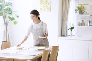 お皿をテーブルに置く女性の写真素材 [FYI02973266]