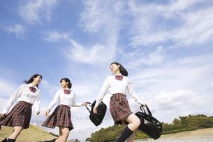 青空をバックに歩く女子高校生たちの写真素材 [FYI02973276]