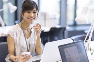 PCの前でスマホを持つビジネス女性の写真素材 [FYI02973284]