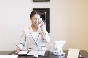 カメラ目線で電話対応をするコンシェルジュの女性の写真素材 [FYI02973288]
