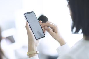 スマートフォンを操作するビジネス女性の手元の写真素材 [FYI02973291]