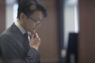 顎に手をあて考えるビジネス男性の横顔の写真素材 [FYI02973293]