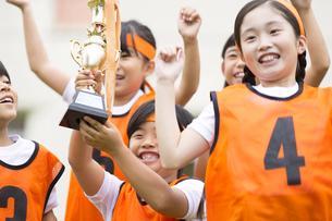 優勝カップを持って喜ぶ子供たちの写真素材 [FYI02973294]