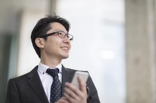 スマートフォンを持ち横を見るビジネス男性の写真素材 [FYI02973301]