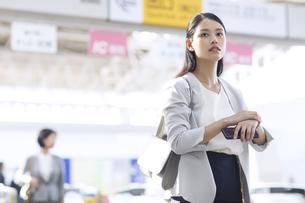 駅で時計を触りながら周りを見るビジネス女性の写真素材 [FYI02973304]