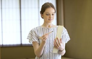 短冊に俳句を書く外国人女性の写真素材 [FYI02973312]