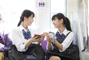 電車で友人と会話をする女子高校生たちの写真素材 [FYI02973313]