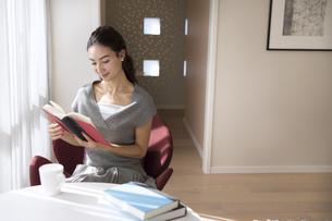椅子に座り本を読む女性の写真素材 [FYI02973331]