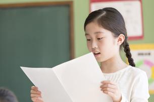 授業中に作文を読む小学生の女の子の写真素材 [FYI02973336]