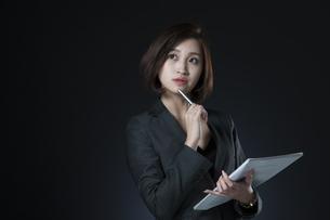 資料とペンを手に持つビジネス女性の写真素材 [FYI02973337]
