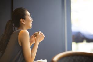 カフェでカップを持ってくつろぐ女性の横顔の写真素材 [FYI02973339]