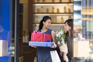 花束やプレゼントボックスを持って店を出る女性2人の写真素材 [FYI02973342]