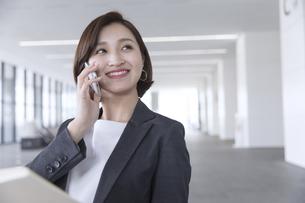 スマートフォンで通話するビジネス女性の写真素材 [FYI02973344]