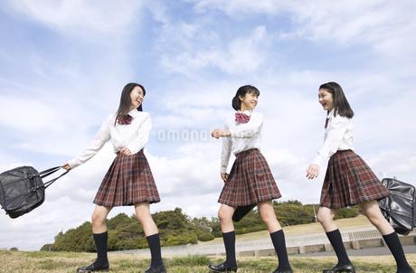 青空をバックに歩く女子高校生たちの写真素材 [FYI02973349]