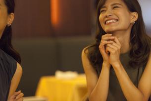 レストランで手を組んで笑う女性の写真素材 [FYI02973351]