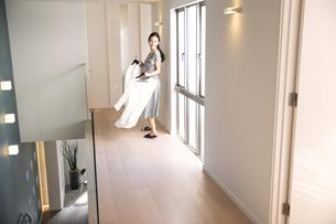 洋服を手に持ち振り返る女性の写真素材 [FYI02973359]