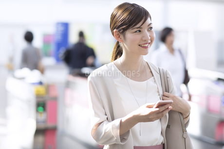 駅の改札付近でスマホを持ち周りを見るビジネス女性の写真素材 [FYI02973369]