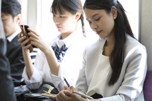 電車で手帳に書き込むビジネス女性の写真素材 [FYI02973371]