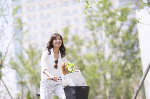 自転車で買い物をする女性の写真素材 [FYI02973374]