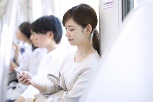 電車の座席に座りスマホを操作するビジネス女性の写真素材 [FYI02973375]
