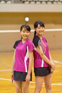 バドミントンのラケットを持って微笑む女子学生2人の写真素材 [FYI02973378]