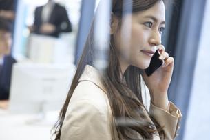 スマートフォンで通話するビジネス女性の写真素材 [FYI02973379]