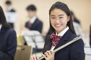 フルートを持って微笑む女子学生の写真素材 [FYI02973383]