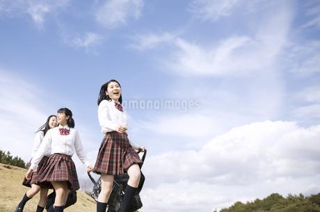 青空をバックに歩く女子高校生たちの写真素材 [FYI02973388]