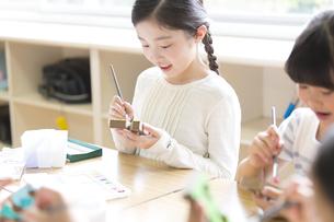 絵具の筆で色を塗る女の子の写真素材 [FYI02973399]