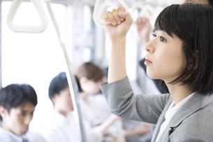 電車でつり革を持ち遠くを見つめるビジネス女性の写真素材 [FYI02973402]