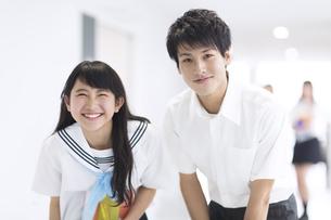 学校の廊下で笑う男子学生と女子学生の写真素材 [FYI02973404]