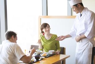 板前と話しながら日本料理を食べる外国人の男女の写真素材 [FYI02973415]