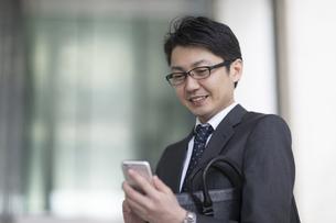 スマートフォンを操作するビジネス男性の写真素材 [FYI02973421]