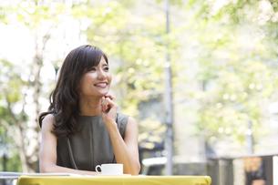 オープンカフェで遠くを眺める女性の写真素材 [FYI02973423]