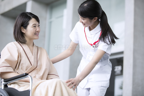 車椅子の患者に添う女性看護師の写真素材 [FYI02973425]