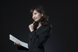 資料とペンを手に持ち微笑むビジネス女性の写真素材 [FYI02973426]