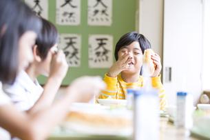 学校の給食を食べながら笑う男の子の写真素材 [FYI02973429]