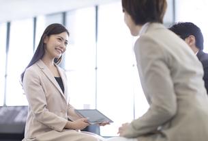 タブレットPCを持ち打ち合わせをするビジネス女性の写真素材 [FYI02973442]
