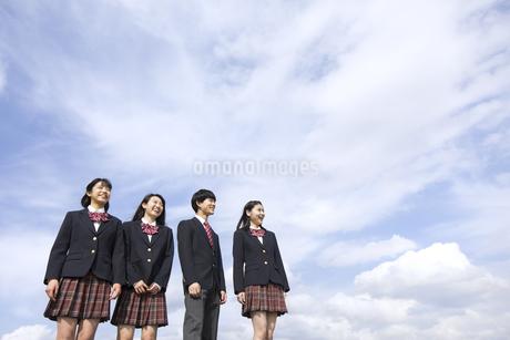 青空をバックに立つ高校生たちの写真素材 [FYI02973444]