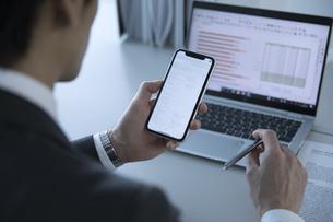 スマートフォンを見るビジネス男性の手元の写真素材 [FYI02973445]