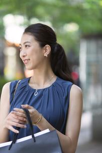 街角で遠くを眺め微笑む女性の写真素材 [FYI02973454]