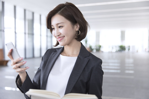 手帳を持ちスマートフォンを操作するビジネス女性の写真素材 [FYI02973462]