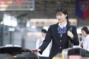 駅の改札に定期券をかざす女子高校生の写真素材 [FYI02973463]