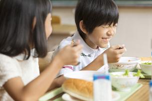 学校の給食を食べながら笑う男の子の写真素材 [FYI02973471]