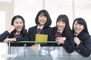 手すりに手を掛けカメラ目線の女子高校生たちの写真素材 [FYI02973473]