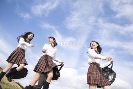 青空をバックに歩く女子高校生たちの写真素材 [FYI02973474]